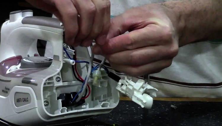 Мастер ремонтирует утюг