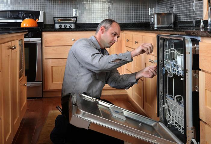 Мастер устанавливает посудомоечную машину