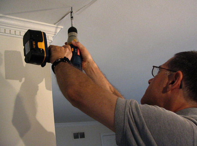 Мастер ремонтирует потолок
