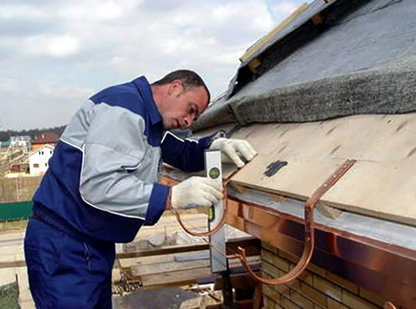 Специалист выполняет монтаж водостока