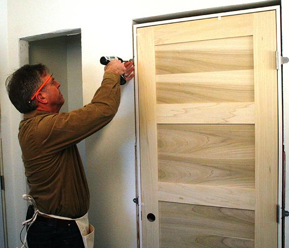 Специалист устанавливает дверь
