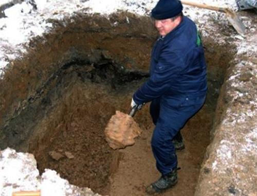 Рабочий копает яму