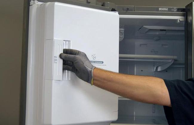Специалист перевешивает дверь холодильника
