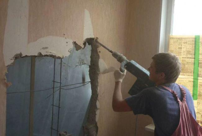 Специалист сносит стену