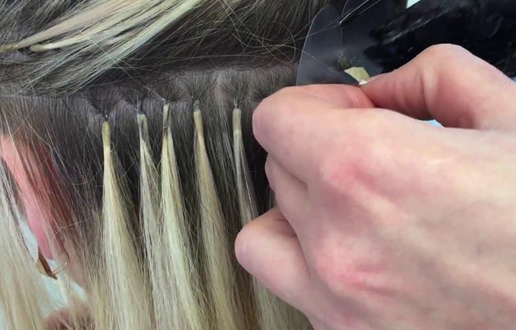 Специалист наращивает волосы капсульным способом