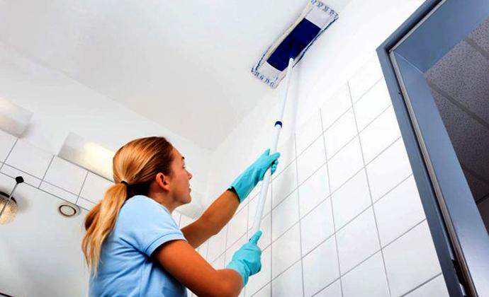 Специалист моет натяжной потолок
