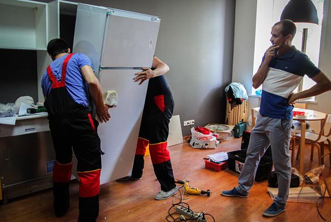 Специалисты устанавливают холодильник