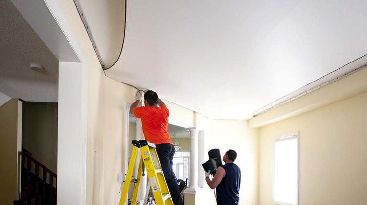 Специалисты работают с натяжным потолком