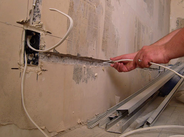 Специалист разводит электрику в квартире