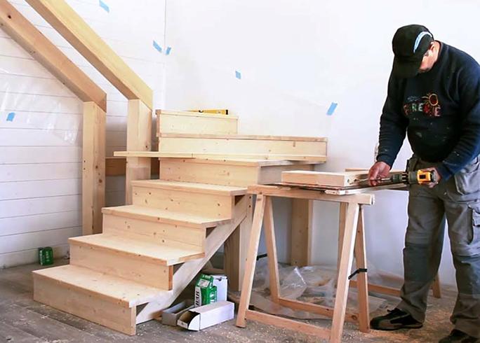 Специалист подготавливает лестницу к монтажу