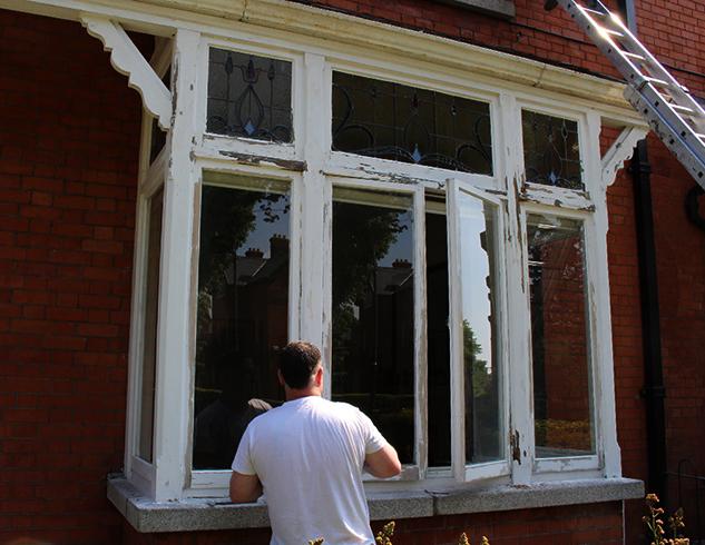 Мастер проводит реставрацию деревянных окон
