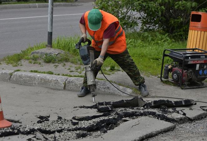 Специалист выполняет демонтаж асфальта