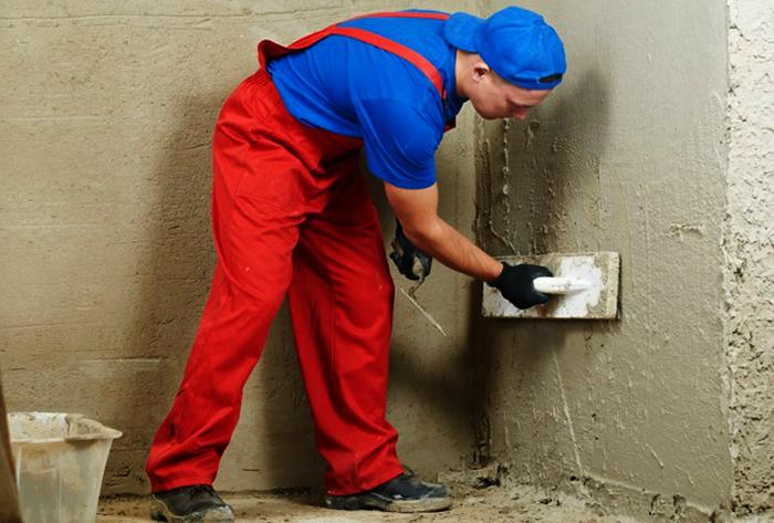 Мастер выполняет штукатурку стен в квартире