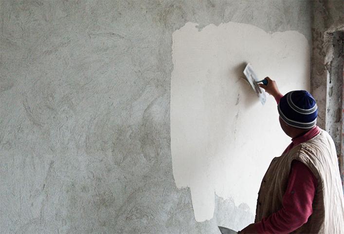 Специалист выполняет штукатурку стен