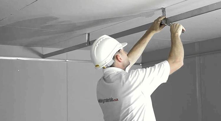Мастер устанавливает натяжной потолок