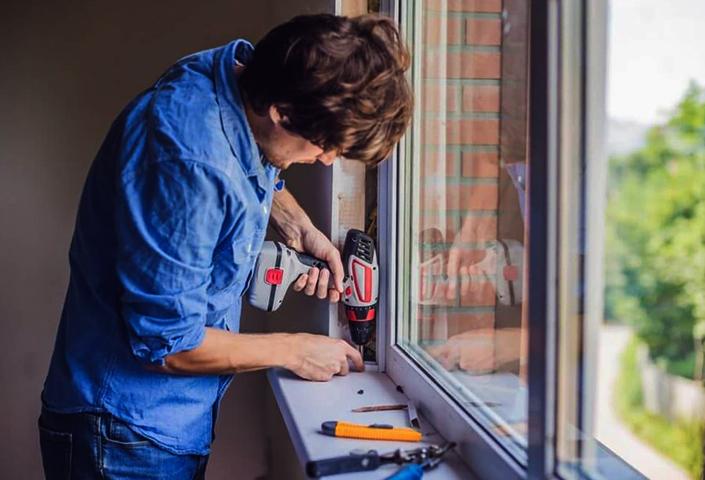 Специалист монтирует энергосберегающие окна