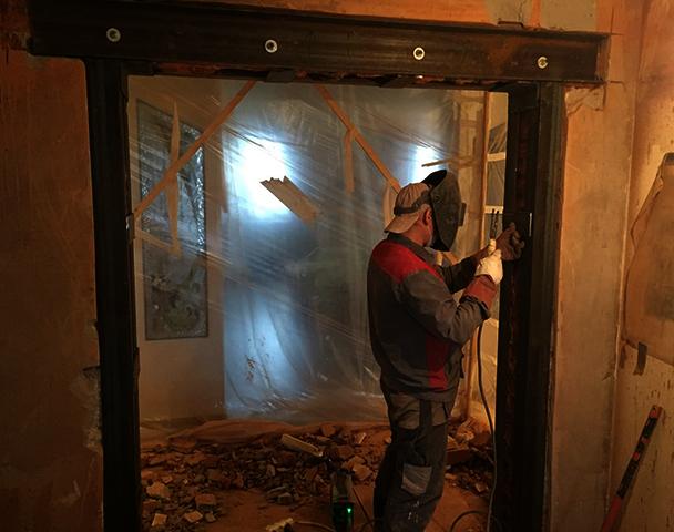 Специалист монтирует проем в стене с усилением