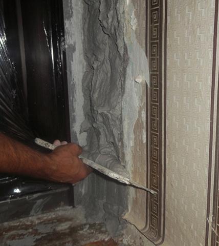 Специалист производит штукатурка откоса двери