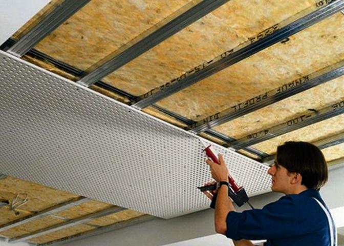 Мастер проводит работы по шумоизоляции потолка