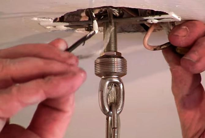 Специалист вешает люстру на натяжной потолок