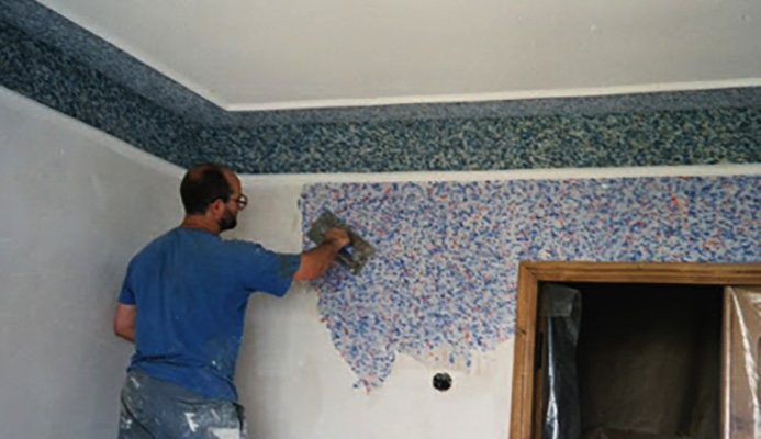 Специалист наносит жидкие обои на стену