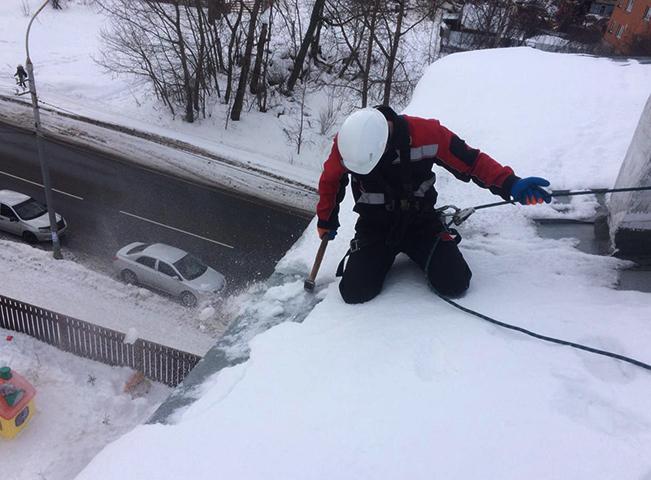 Специалист убирает снег с крыши
