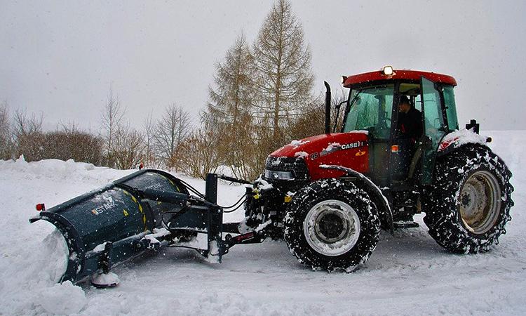 Трактор чистит территорию от снега