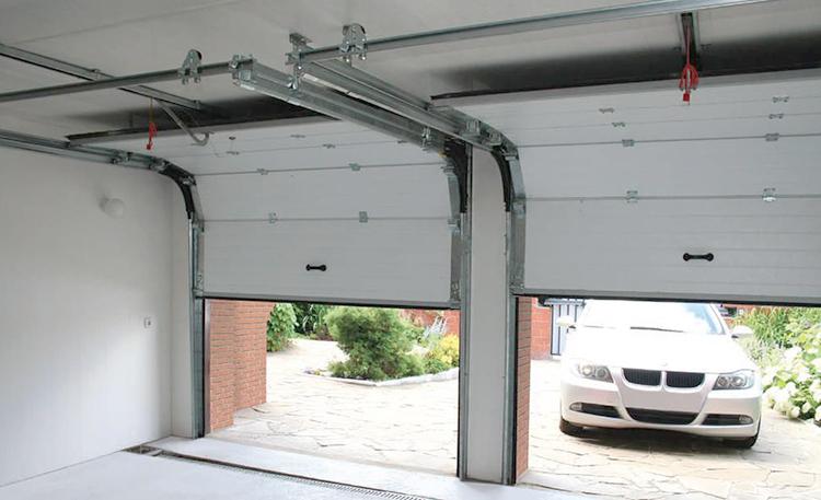 Автомобиль заезжает в гараж с воротами-рольставнями