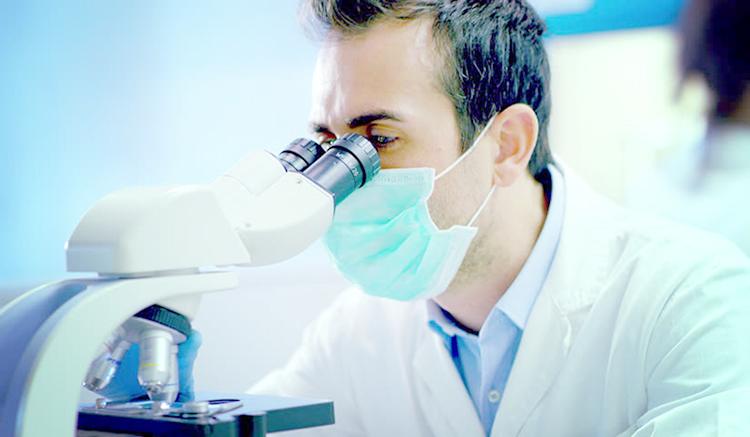 Доктор изучает ткань под микроскопом
